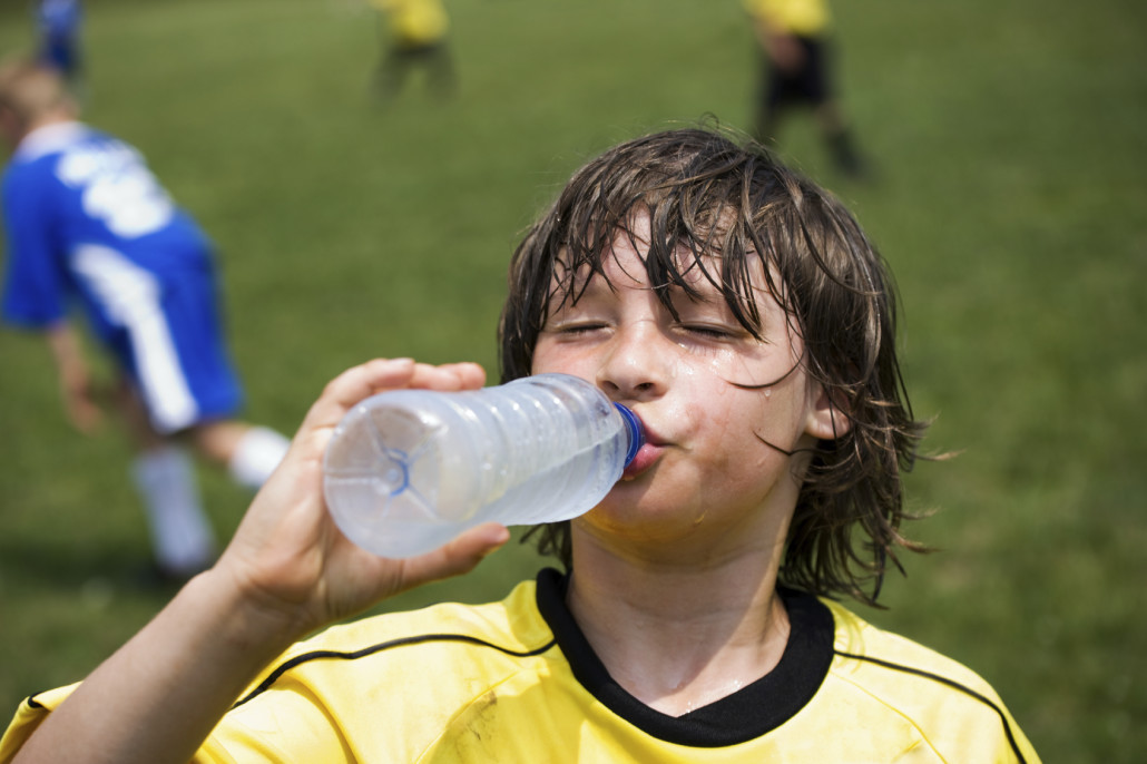 Thirsty soccer player drinking water on the sidelines of playing field.